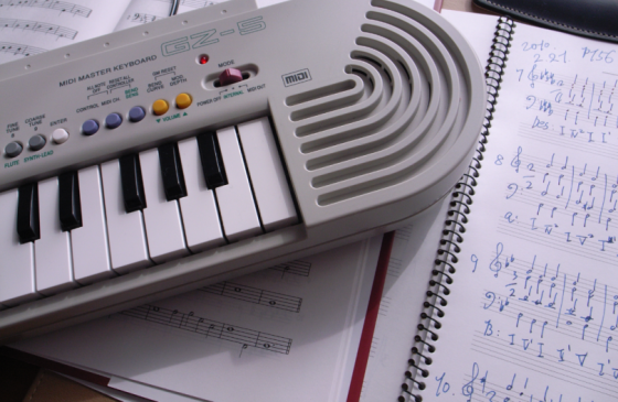 image presenting a sheet music and a MIDI keyboard, in a web page related to music research, music technology and the YMusic search engine